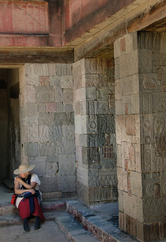 Woman in Mexican dress with hat sits in the shade of the carved pillars of the Pyramid of the Moon