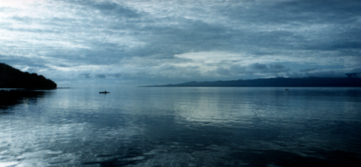 A fisherman in an outrigger canoe can be seen in a panoramic photo of the ocean with islands at dawn with an overcast sky.