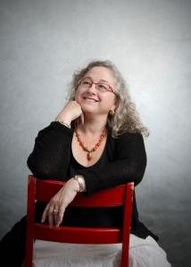 Picture of Mara with long curly grey hair sitting on a red chair turned backwards.